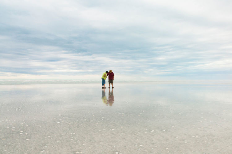 Couple standing at beach against cloudy sky