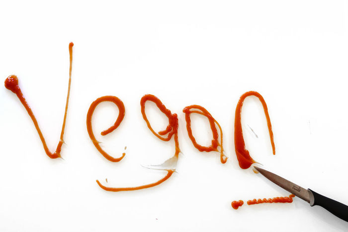 The word 'Vegan' shown as lifestyle graffiti Alphabet Close-up Collage Crueltyfree Food Lifestyle Metaphor No People Sign Slogan Sustainable Living Sweet Food Text Tradition Vegan Vegan Food Veganism White Background Words
