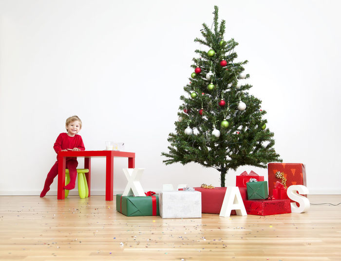 Portrait of boy on red christmas tree