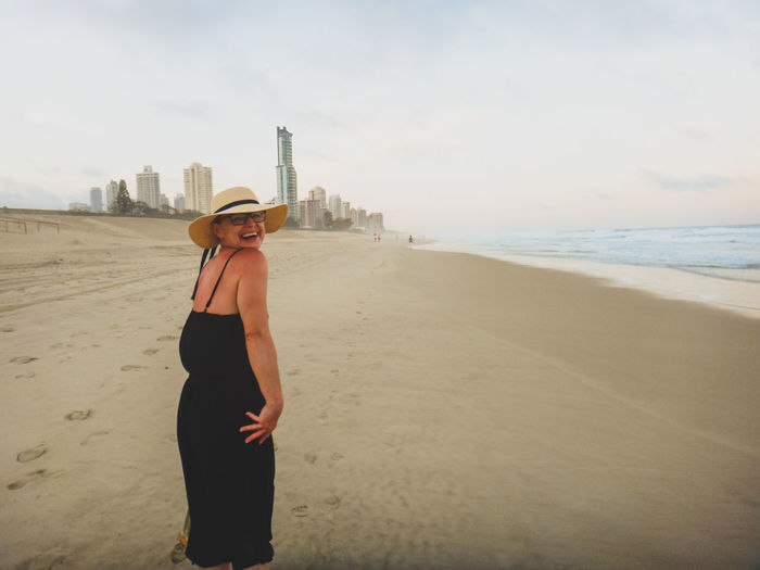 Happy Woman Wearing Black Dress Standing At Beach By City Against Sky