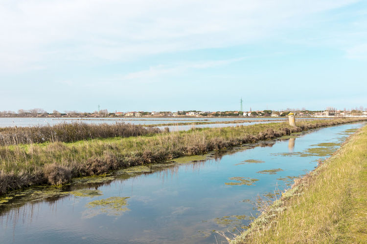 Italy, Cervia. This city is famous for its salt. Saltern date back to ancient times. Beauty In Nature Cloud - Sky Day Environment Grass Lake Landscape Nature No People Non-urban Scene Outdoors Plant Reflection Scenics - Nature Sky Swamp Tranquil Scene Tranquility Water Wetland