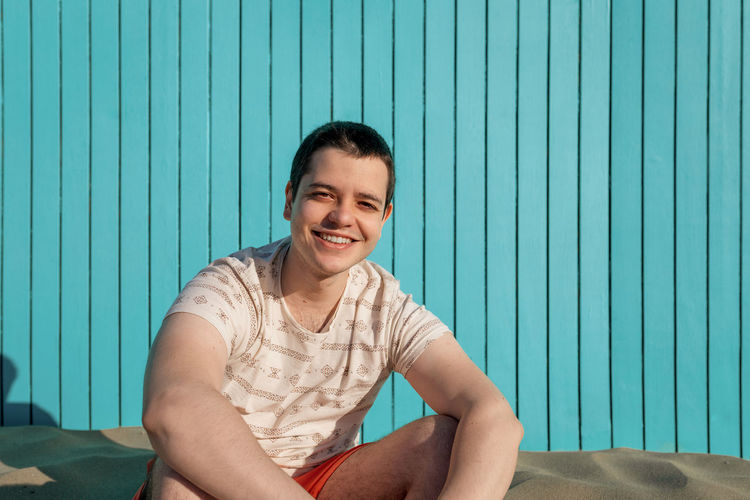 Portrait of smiling young man sitting against wall