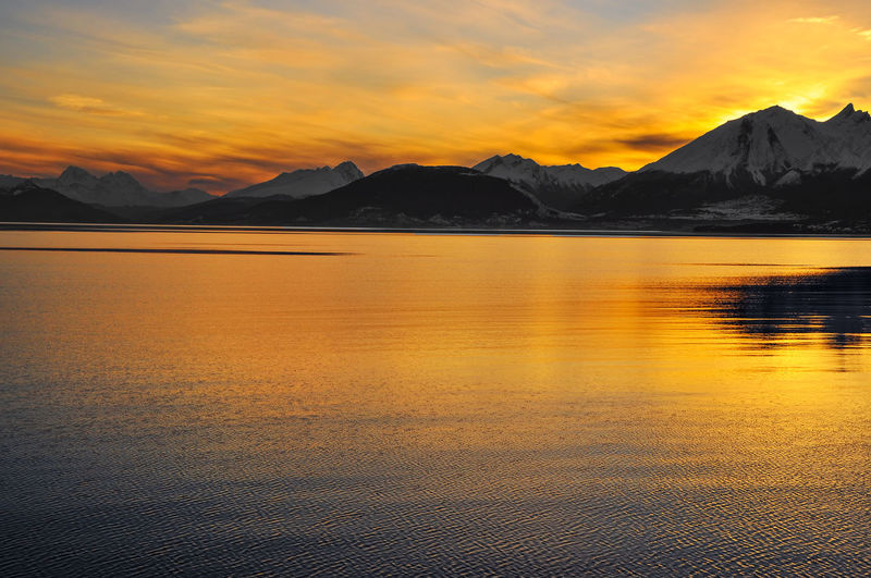 Scenic view of beagle channel against mountains during sunset