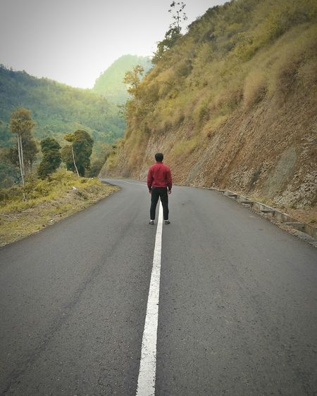 Rear view of man on road against mountain