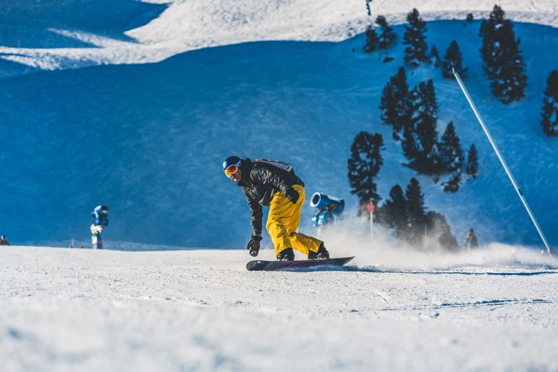 Man snowboarding on snow covered field