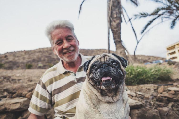 Senior man holding pug