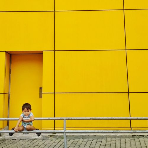 Boy hanging on railing against yellow building