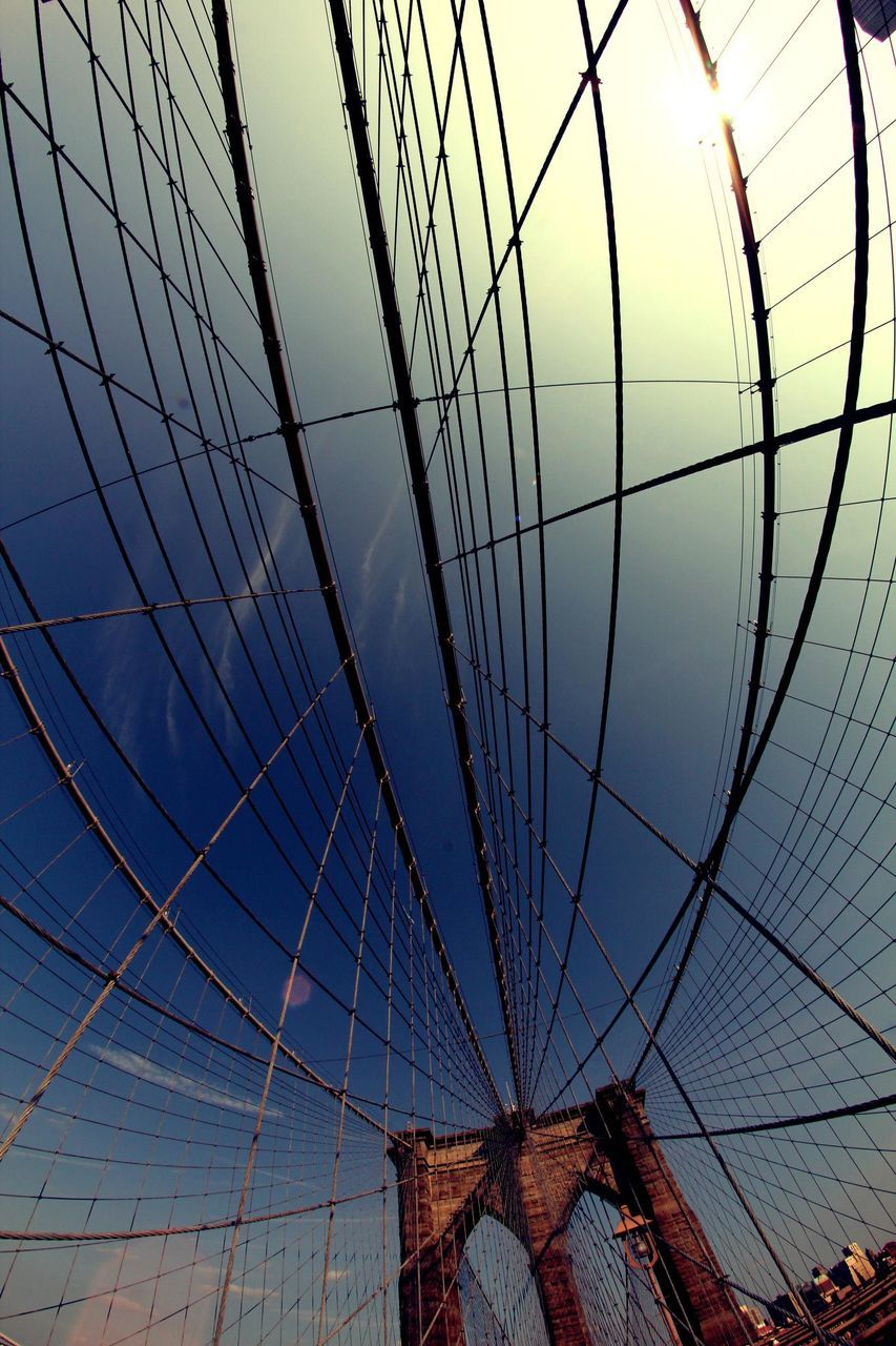 architecture, low angle view, built structure, connection, sky, bridge - man made structure, no people, travel destinations, suspension bridge, outdoors, skyscraper, sunset, day, building exterior, clear sky, city