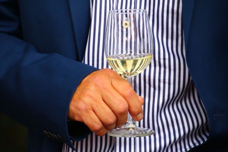 Midsection of man holding wineglass