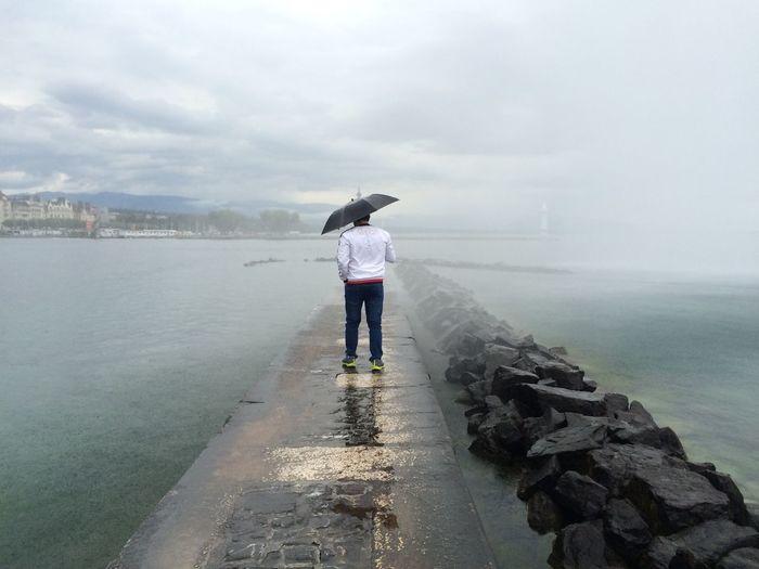 Full length rear view of man with umbrella walking on pier amidst sea during rainy season