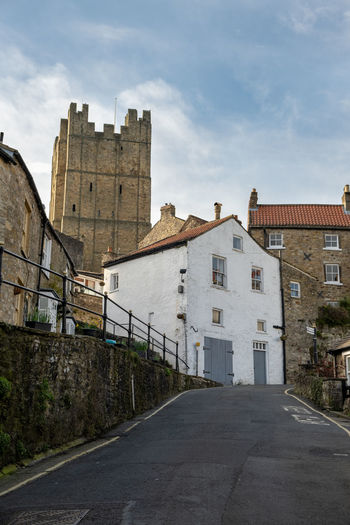 A view looking up along a road of richmond castle with the castle walk and houses in the foreground