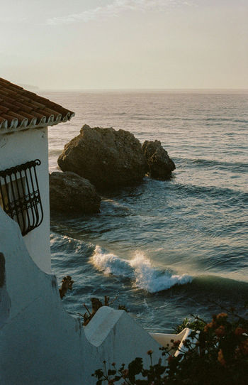 Waves crushing on the shore at the sunrise with house on the side