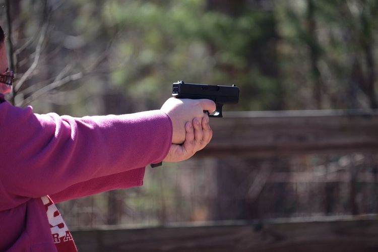 Side View Of Woman Aiming With Handgun