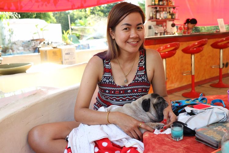 Portrait of young woman with dog sitting at restaurant