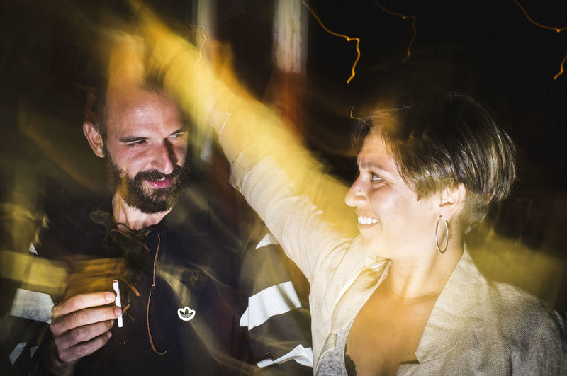 Man and woman with arms raised at night