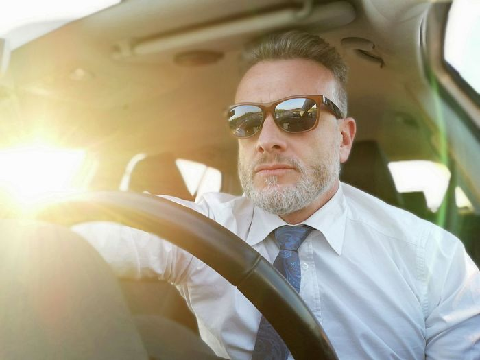 Man wearing sunglasses while driving car