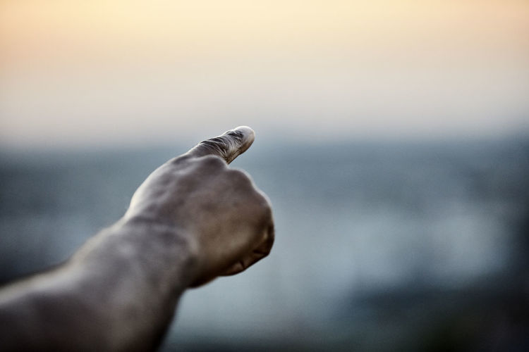 Close-up of hand holding stick against sky during sunset