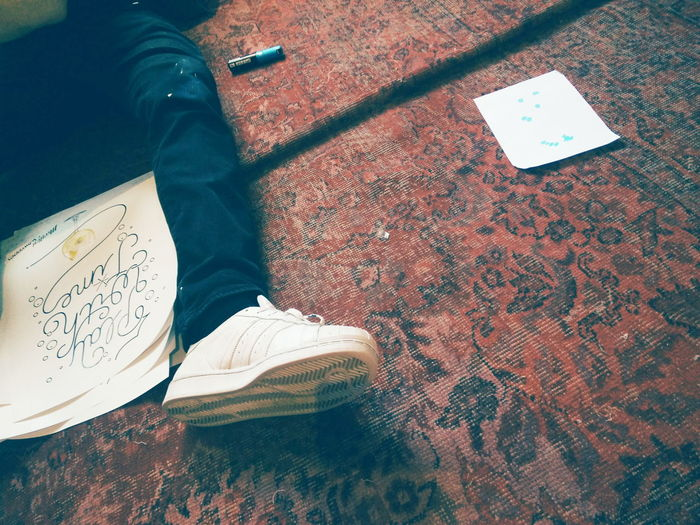 Low section of man lying by drawing on carpet