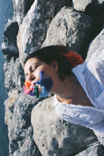 Woman with closed eyes holding tassel in mouth while sitting on rock at beach