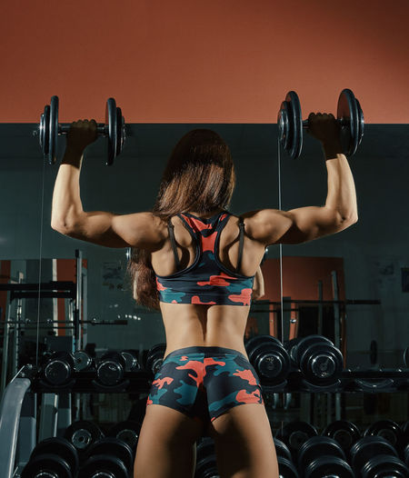 Rear View Of Young Woman Exercising In Gym