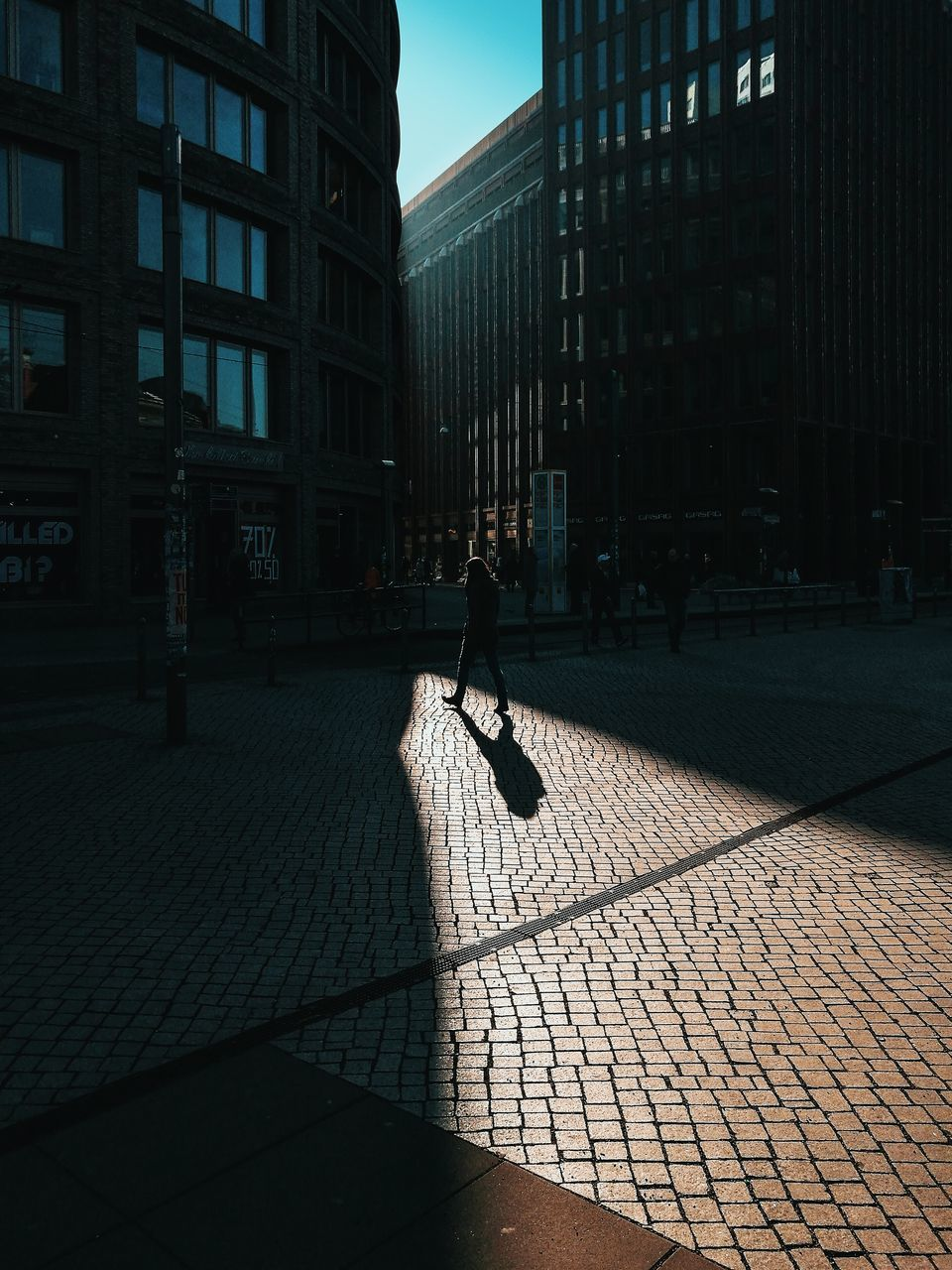 architecture, building exterior, city, built structure, full length, shadow, one person, city life, day, real people, outdoors, sunlight, skyscraper, travel destinations, people