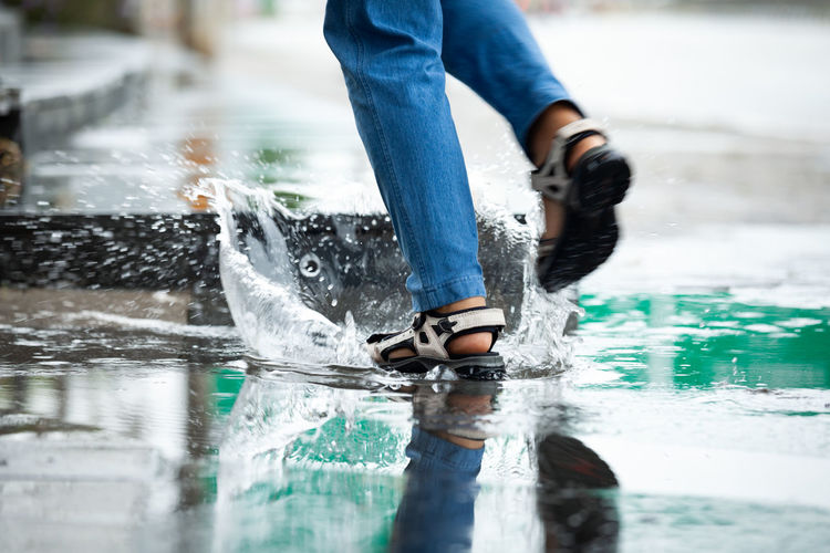 Low section of person splashing water walking on road