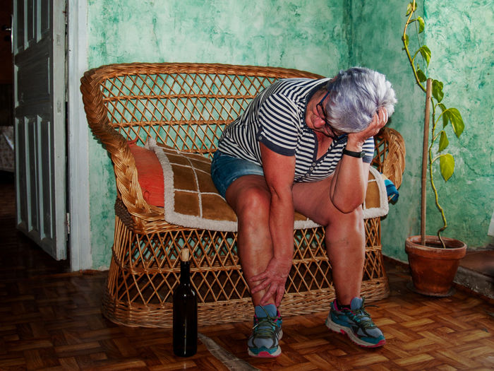 Drunk woman sitting on chair at home