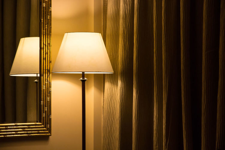 Standing lamp and reflection in a mirror of a hotel room with closed dark curtains. Warm incandescent light. Concept: anonymous, sterile, alone, hotel room interior design, travel, dim light, simple Lighting Equipment Electric Lamp Illuminated Indoors  Lamp Shade  No People Home Interior Electricity  Curtain Electric Light Domestic Room Light Wall - Building Feature Floor Lamp Architecture Absence Design Home Showcase Interior Glowing Decoration Hotel Room Anonymous Closed Curtains Dim Light Simple
