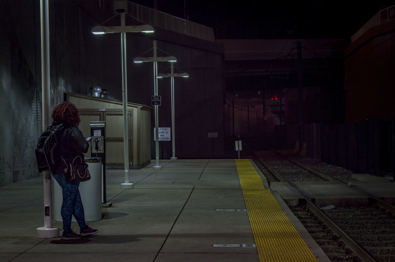 Rear View Of Woman Standing At Railroad Station Platform