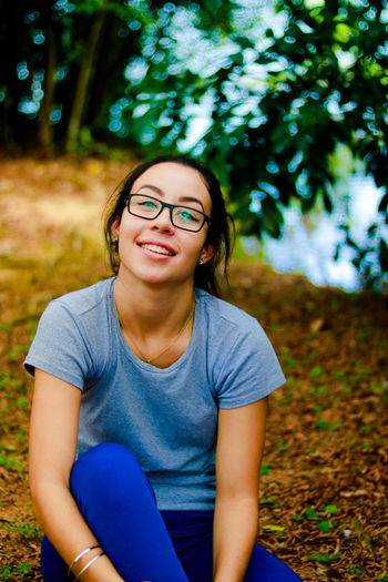Portrait of smiling young woman sitting on field in park