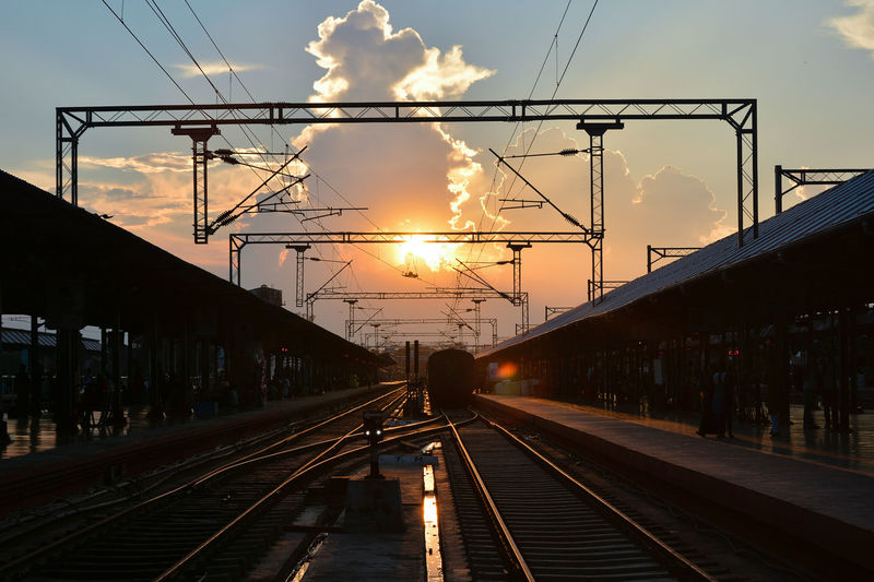 Railroad tracks against sky at sunset