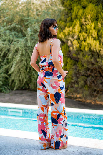 Portrait of woman standing by swimming pool