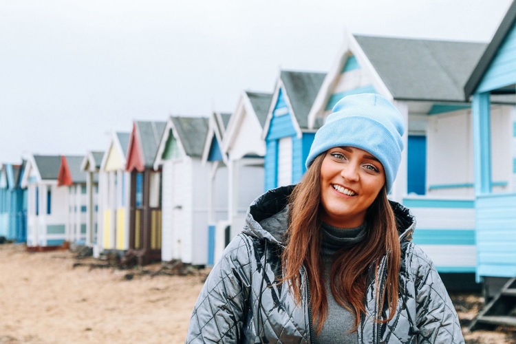 Portrait of smiling young woman standing against beach huts