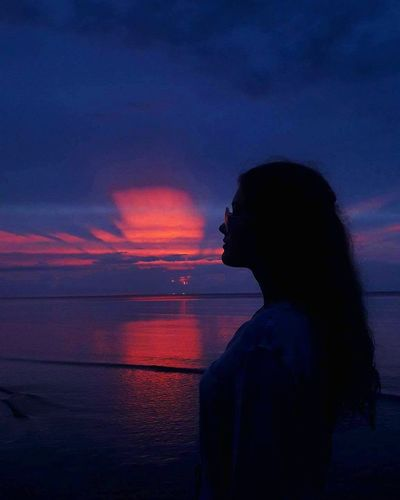 Side view of silhouette woman against sea during sunset