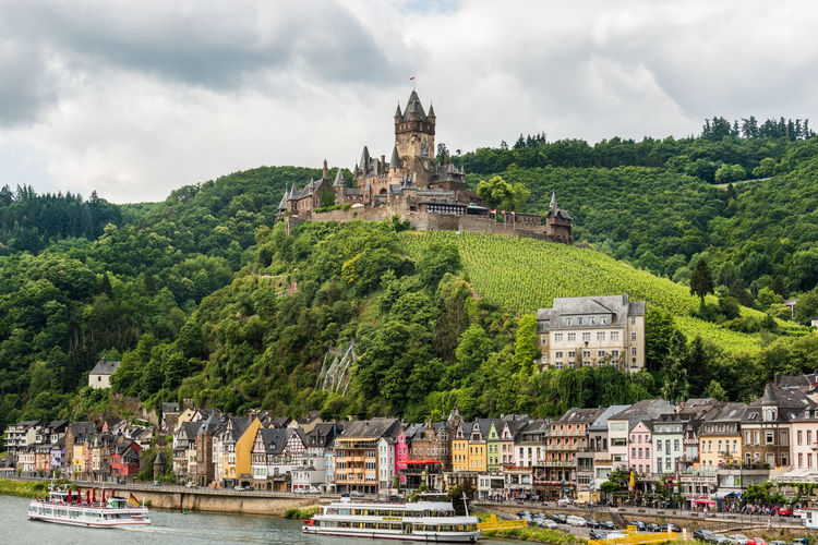Boats moored at riverbank against cochem imperial castle on mountain