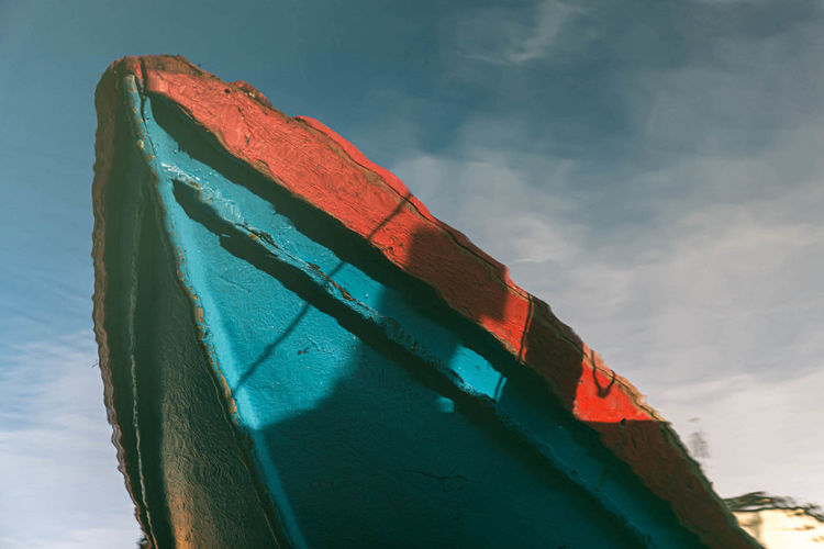 Low angle view of reflection of boat hull  in water against sky