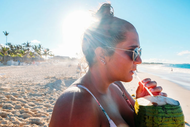 Close-Up Of Woman Drinking Coconut Water At Beach During Sunny Day