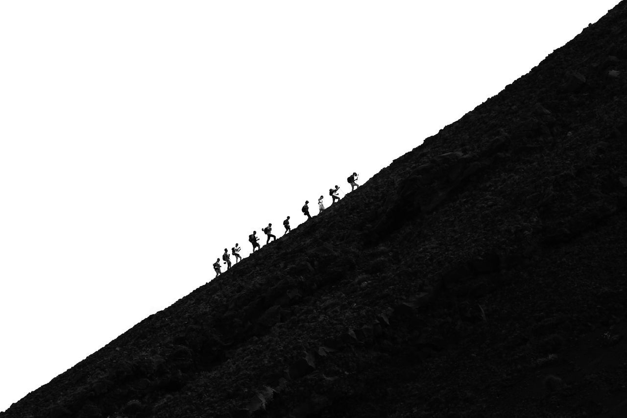 Low Angle View Of People Hiking On Hill Against Clear Sky