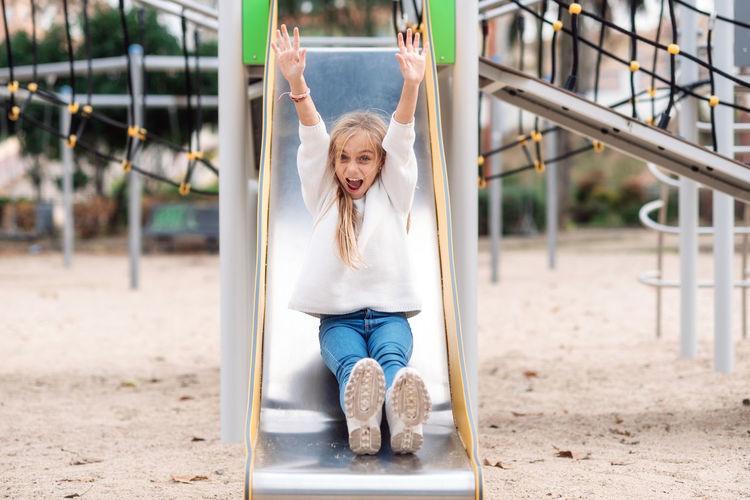 Portrait of girl sliding in playground
