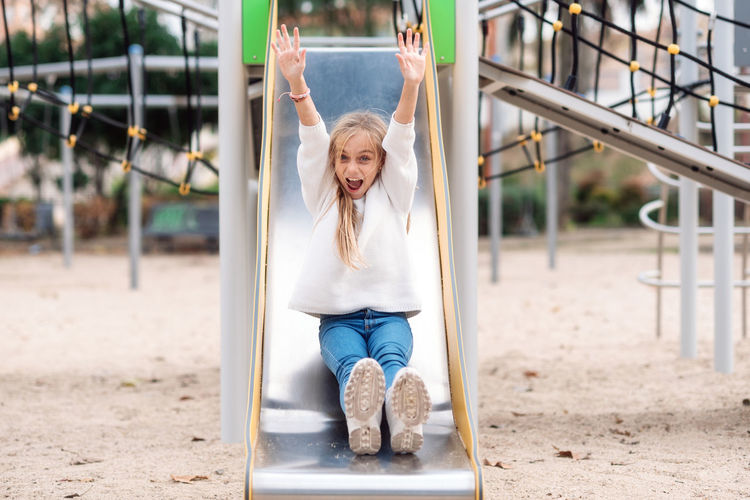 Portrait of happy girl sitting on slide at playground