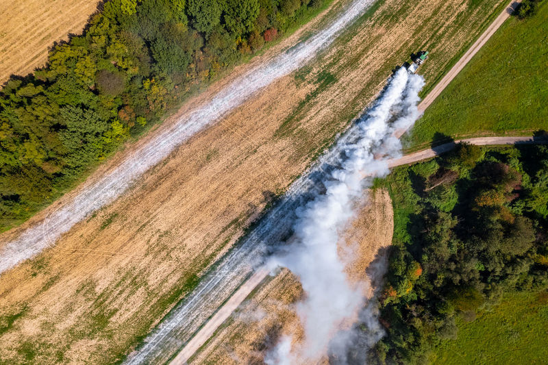 Aerial view of a tractor spreading lime on fields to improve soil quality after the harvest.