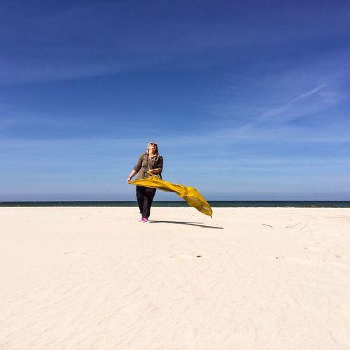 Cheerful woman holding scarf while walking on plaza bialogora beach