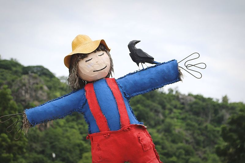 Scarecrow by mountain against sky