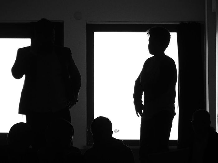 Silhouette businessman with male colleague in office during presentation