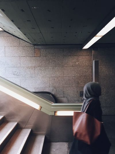 Side View Of Woman Walking In Illuminated Subway