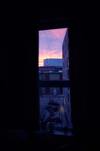 Silhouette buildings against sky during sunset seen through window