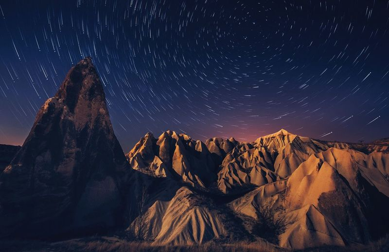 Panoramic view of mountains against sky at night