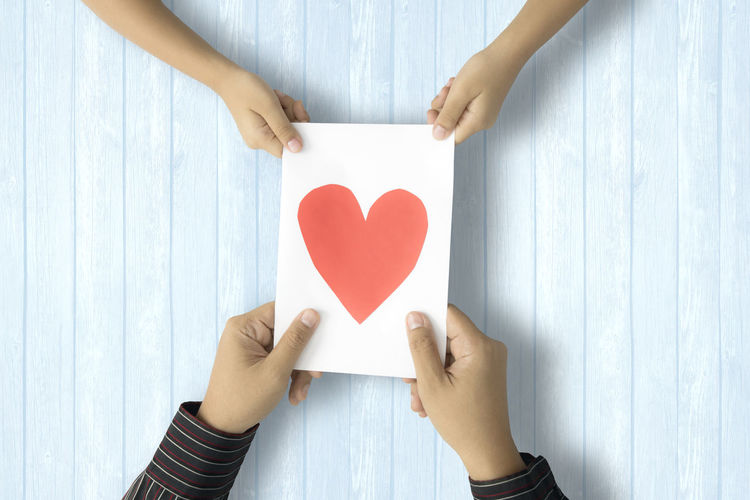 Cropped image of couple holding paper with heart shape on table