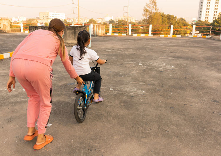 Rear view of women riding bicycle