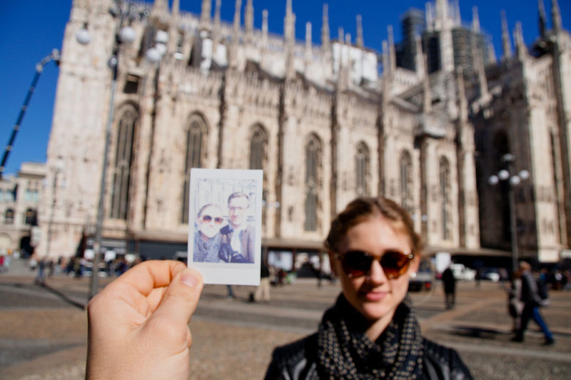 Cropped hand of man holding photograph with woman in background against milan cathedral